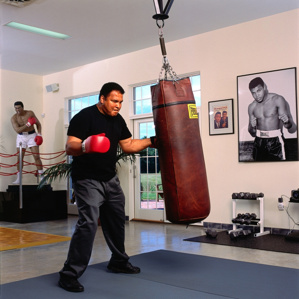 Ali hitting heavy bag in his home gym neil leifer
